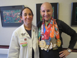 """With Dr. Nerenstone showing off all my medals earned while undergoing breast cancer treatment up until my final chemo """"therapy"""" (Aug-Jan). 3 full marathons (including 2 world majors), 5 half marathons, 1 10-miler, 3 10-k's, 5 5-k's, plus a Dumbo, Goofy, Dopey and a Coast to Coast!"""